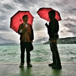 Year 2, Day 108: Colin Howard (left) and Ricky Cometa (right) in a rainstorm by Lake Annecy. | Photo: Maija Burnett