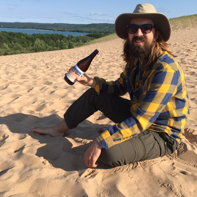 SoLArc Brewing co-founder and CalArts alumnus Archie Carey enjoying a bottle of 'Dunes' at Sleeping Bear Dunes National Park in Michigan. | Photo courtesy Archie Carey