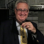 President Steven D. Lavine shows off his new Court of the Lord Chamberlain medal. | Photo courtesy SCVTV