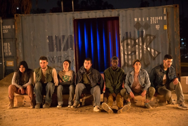 Seven actors sit in a row in front of an industrial background.