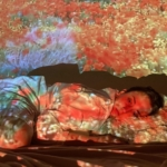 Young woman lays head on pillow with neutral expression. An image of a red flowers and other plants are projected over the scene.