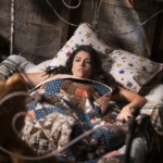 Cecily Strong in a floral patterned bed